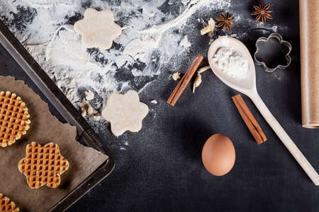 rolling paper: Waffle ingredients like eggs, flour, cinnamon, anise, rolling pin, paper on blackboard from the top Stock Photo