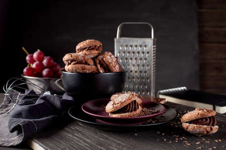 Italian maroni cookies on the plate and bowl with grapes, cloth, notebook on dark old wooden background