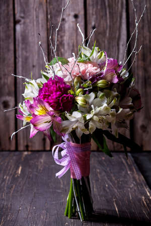 Pink bouquet from gillyflowers and white alstroemeria on old wooden background Stock Photo