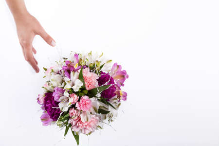 Hand receiving a pastel bouquet from pink and purple gillyflowers and alstroemeria Stock Photo