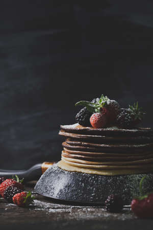 castor: Chocolate pancakes in black pan with organic fruits like strawberries, blackberries and castor sugar on old wooden table Stock Photo
