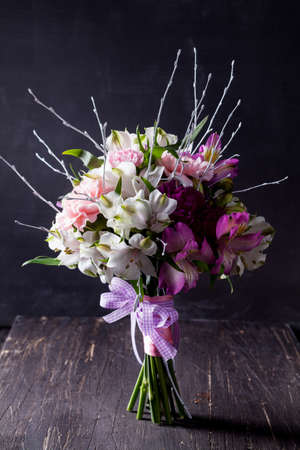 Pink bouquet from gillyflowers and white alstroemeria on blackboard and old wood
