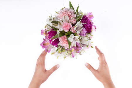 Hands receiving a pastel bouquet from pink and purple gillyflowers and alstroemeria