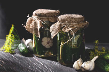 Rustic jars of  pickled cucumbers with garlic and dill on black table