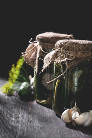 Rustic jars of  pickled cucumbers with garlic and dill on black table, vertical