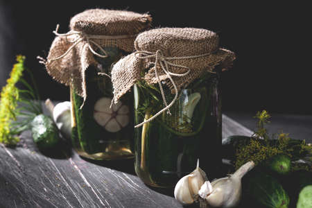 Two jars of pickled cucumbers with garlic and dill on black table
