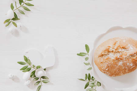 Natural Easter decoration with white wood and green leaves on wooden table with bread on white plate Stock fotó