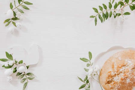 Simple Easter white and green decoration with wooden rooster and plate with homemade bread