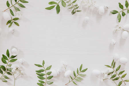 White and green Easter decoration with flowers, leaves and little eggs on white wood