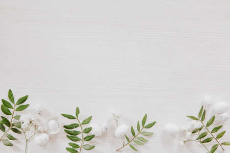 White and green Easter decoration with flowers, leaves and little eggs on white wood, flat lay Stock fotó