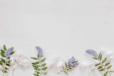 White and green Easter decoration with grape hyacinths, leaves and little eggs on white wood