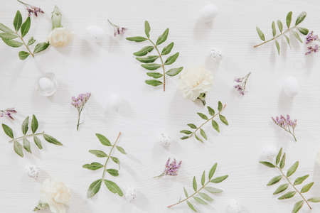 Fresh green leaves, little eggs and violet and yellow flowers on white wooden background Stock fotó