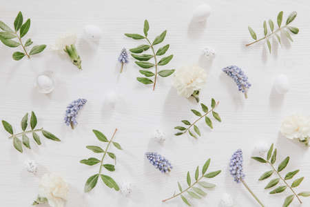 Fresh green leaves, little eggs, grape hyacinths and gillyflowers on white wooden background Stock fotó