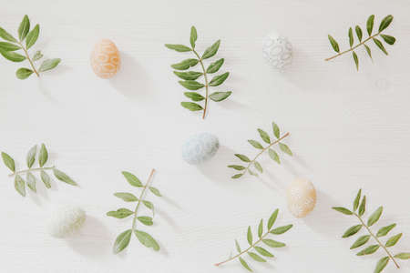 Easter pattern from green leaves and little colorful eggs on white wooden background