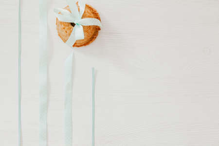 Easter muffin with blue ribbons on white wooden table