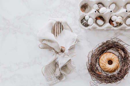Natural Easter table decoration with silverware and cup cake in a wreath on marble table