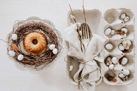 Natural Easter table decoration with silverware and cup cake in a wreath on wooden table
