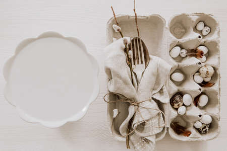 Natural Easter table decoration with silverware and plate on wooden table