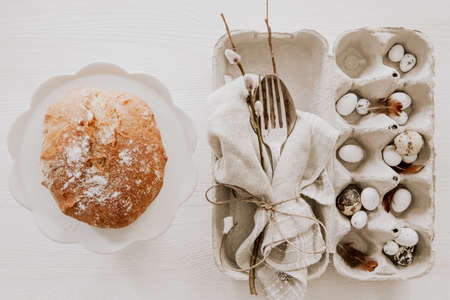 Natural Easter table decoration with silverware and plate with bread on wooden table