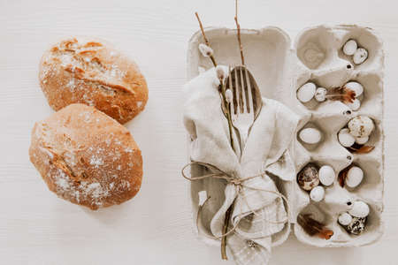 Natural Easter table decoration with silverware and bread on wooden table