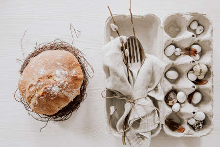 Natural Easter table decoration with silverware and plate with bread in a wreath on wooden table Stock fotó
