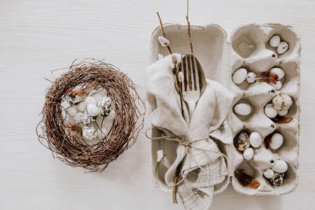 Natural Easter table decoration with silverware and eggs in a wreath on wooden table Stock fotó