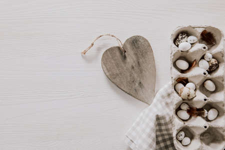 Easter decoration with wooden heart and egg box with napkin on wooden table