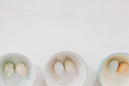 Beautiful pastel eggs in decorative bowls on the bottom of white wooden background