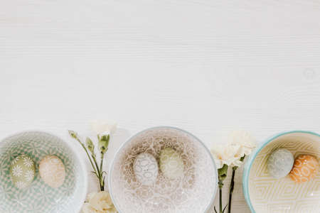 Beautiful pastel eggs in decorative bowls and gillyflowers on the bottom of white wooden background