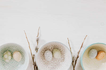 Beautiful pastel eggs in decorative bowls and fluffy willow on the bottom of white wooden background