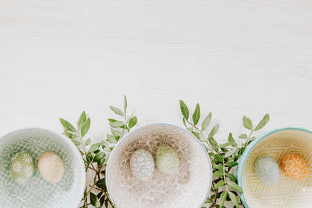 Beautiful pastel eggs in decorative bowls and green leaves on the bottom of white wooden background