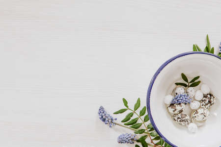 Simple Easter decoration with eggs in a bowl and grape hyacinths in the corner of white wooden background