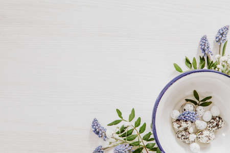 Simple Easter decoration with eggs in a bowl and grape hyacinths with gypsophila paniculata in the corner of white wooden background Stock fotó