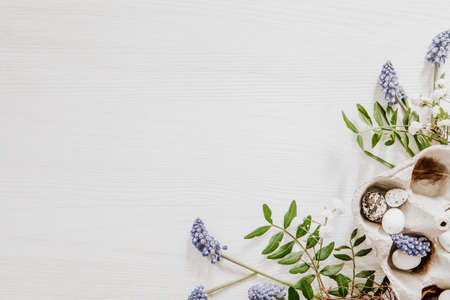 Natural Easter decoration with eggs in a egg box and grape hyacinths with gypsophila paniculata in the corner of white wooden background