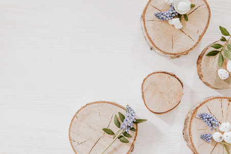 Simple Easter decoration with wooden blocks with grape hyacinths, little eggs and green leaves on white wooden table Stock fotó