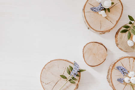 Wooden blocks with grape hyacinths, little eggs and green leaves on white wooden table