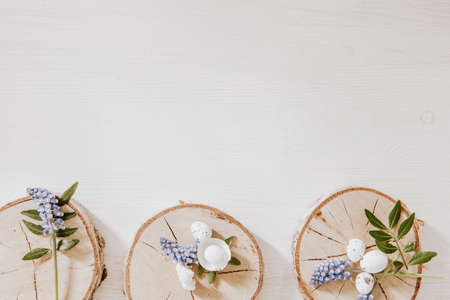 Wooden blocks with grape hyacinths, little eggs and green leaves on the bottom of white wooden table