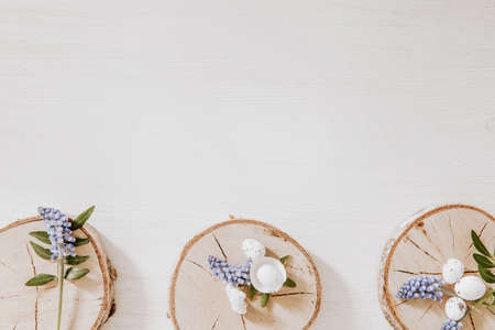 Spring Easter decoration with wooden blocks with grape hyacinths, little eggs and green leaves on the bottom of white wooden table