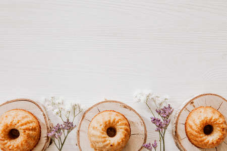 Muffins on wooden blocks lying on wooden table with violet and white flowers