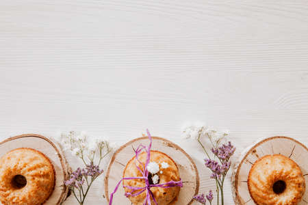 Wooden blocks with cupcakes, violet and white flowers on the bottom of white wooden background Zdjęcie Seryjne