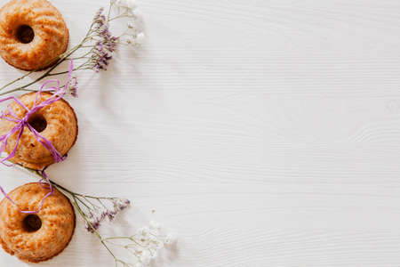 Muffins with ribbon, white and violet flowers on the side of white wooden table