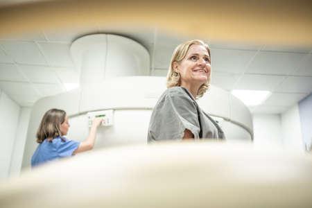 Portrait en contre-plongée d'une vieille femme confortable et amusée souriante après une IRM dans une clinique médicale. Les infirmières aident la vieille dame à l'hôpital après le traitement. Les personnes de race blanche et les soins de santé. Banque d'images