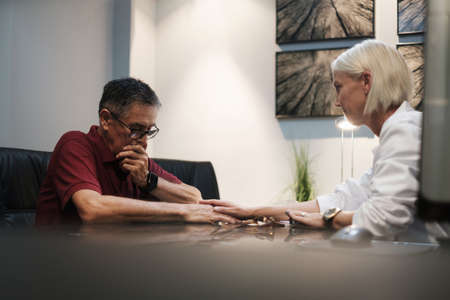 Empathic Doctor Deliver Bad Health News to Senior Patient Stock Photo
