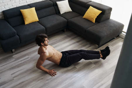 A muscular young good looking white male is working out on the floor of his house doing an ABS routine and training his core muscles. Shirtless fitness instructor performs a knee tuck exercise at home