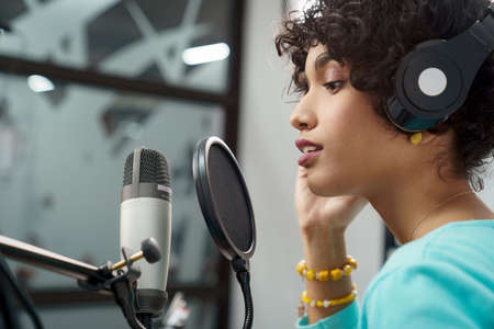 Attractive Young Black Woman Singing Into Microphone in Recording Studio Session. African American Female and podcast host with curly hair in Radio Show Talking to Microphone while wearing headphones Stock Photo