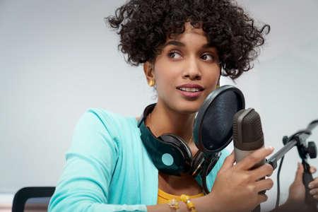 Bella giovane donna nera che fa una registrazione di podcast online per il suo spettacolo online. Attraente donna d'affari afroamericana millenaria che utilizza le cuffie davanti al microfono per un programma radiofonico.