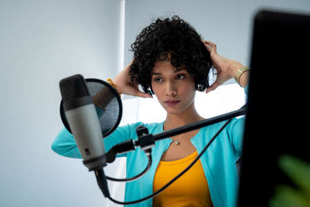 Good looking young black female making an online podcast recording for her online show. Attractive millennial African American business woman using headphones in front of microphone for radio program. Banque d'images - 121699116