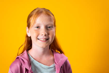 A Caucasian teenager girl with red hair and freckles posing for a portrait over yellow background with copy space. Concept of confident and assertive young females. Gender equality and womens rights.
