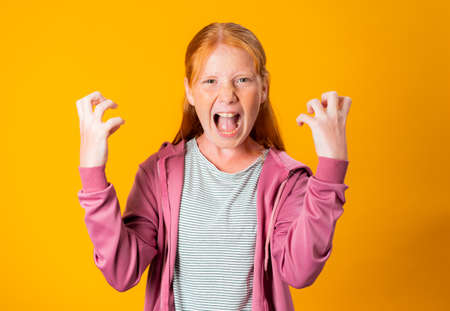 A young Caucasian redhead girl throws hysterical, angry tantrum, screaming and moving her hands in violent way while having a very angry face. Concept of anger management. People with no self control