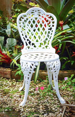 chair outdoors / vintage white chair stand in the garden flowers with green plant background